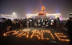 """Mongolian journalists holding cards pose next to candles which were placed to form the phrase """"I am ... - REUTERS/B. Rentsendorj"""