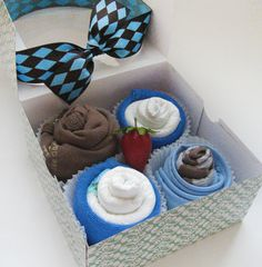 "Cupcake box contents:    (1) bodysuit  (1) Pair of socks  (1) Bib  (2) diapers - Size: 1  (2) Super soft washcloths  (1) Faux strawberry  (1) Colorful bakery box tied with a beautiful ribbon. ""Ingredients"" are printed on the side of the cupcake box."