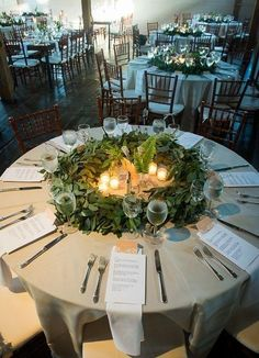 Beautiful round wedding table setting - with greenery centerpiece