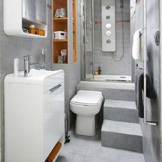 Aménagée en longueur cette salle de bain gris clair est très fonctionnelle avec des rangements compacts et une douche confort.
