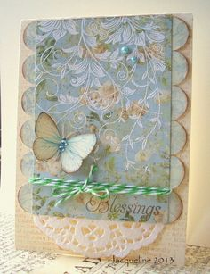 handd made card: Blessings by Jacqueline ... luv the white embossed swirly vine on this sweet blue print paper ... circle punched paper attached as a scalloped edge ... doily, twine & pearls ... butterfly rests on top ... gorgeous card ... Hero Arts vine stamp ...