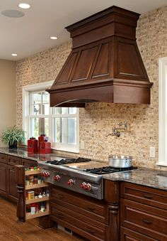 Traditional Kitchen with Wood Hood, no upper cabinetry and decorative turn posts that hide secret storage for spices and other goods for cooking. Features a pot filler and wall to wall backsplash. Designed by Knight Construction Design - Dura Supreme Cabinetry