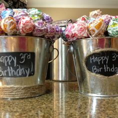 Dum-dum Centerpieces using floral foam wrapped in a brown paper sack fitted in a tin bucket...super easy, cute and colorful.