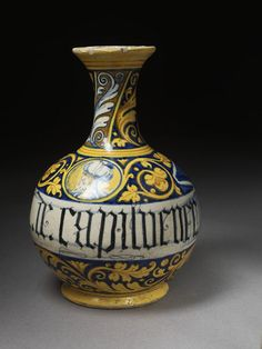 Drug bottle, 'A DE CAPILVENERE' painted around waist, made in Faenza, 1550-75, tin-glazed earthenware | V&A Search the Collections