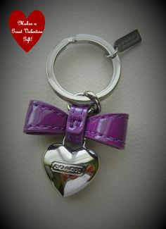 "Perfect Little Gift for Valentines Day or Any Special Occasion. This cute Key Ring by the Iconic Coach is made out of Silver Plated Brass and has a Purple Patent Bow. Retails at $48.00. This is a Great Bargain that will be Treasured and Appreciated by whomever receives it! Other Details: 1 1/4"" a..."