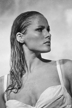 20 most iconic beach hair of all time: Ursula Andress keeps it cool with a slick back wet hair look.
