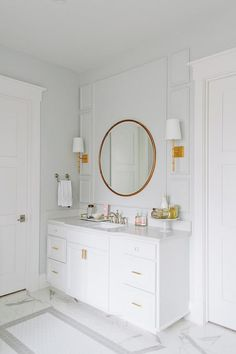 Stunning bathroom features walls painted light gray, Benjamin Moore Wickham Gray, accented with gray trim moldings lined with a white washstand adorned with gold pulls topped with faux marble by I Marmi di Rex placed under a gold convex mirror, Wisteria Gilt Minimalist Mirror, illuminated by Worlds Away Molly Gold Leafed Wall Sconces alongside a faux white marble floor.