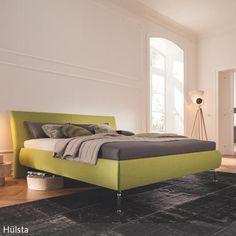 Ein apfelgrünes Polsterbett setzt einen angenehmen Farbakzent im Wohnzimmer mit weißen Wänden und hellem Parkettboden. Originell wirken der Nachttisch und  …
