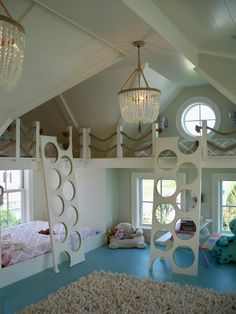 Fabulous attic bunk room with a pair of Ro Sham Beaux Malibu Chandeliers hung from the wood planked ceilings over a turquoise blue painted floor layered with a thick shag rug. The bunk room features a pair of bunks, dressed in Serena and Lily Bedding, built into the dormer ceiling with round windows and rope strung railings alongside a pair of white ladders with round treads. A third bed stands below the left hand bunk with a picnic style play table below the bunk to the right.