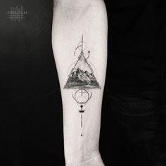 Decorative mountain rage tattoo on forearm by Okan Uckun