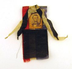 """Abraham Lincoln commemorative ribbon features a small sepia-toned photograph of the President with a beard and wearing a dark suit, bow tie, and white shirt. The image is encased in a gilt metal frame. The frame is mounted on a strip of red, white, and blue silk with embroidered white stars. A black and white silk bow is attached above the frame and a swatch of black crepe is attached below. A paper maker's label is adhered to the back and reads, """"Made by S.A. Blake; 407 Broadway, New York"""