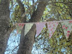 pink and green bunting strung from trees in the garden to set the scene