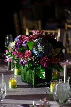 Gorgeous centerpiece with a mixture of purple flowers, plus pops of green cymbidium orchids.