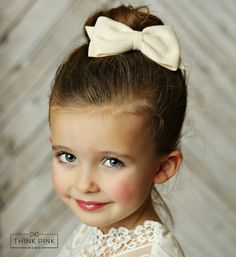 """Playful and Proper coalesce to create this daintily sweet bow! Our cute """"School Girl"""" Felt Bow Clippie in Ivory is handcrafted approximately 4.5-5 inches in size. It is set on an easy-open hair clippi"""