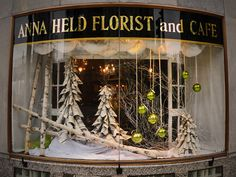 "Christmas Windows at Anna Held Florist and Cafe Isn't this Christmas window display splendid? And the ""trees"" are made of rolled newspapers! Florist Window Display, Store Window Displays, Shop Displays, Retail Displays, Merchandising Displays, Christmas Store Displays, Holiday Store, Christmas Window Display Retail, Christmas Windows"