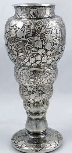"Tiffany Acid Etched Vase Circa 1900  An unusual Tiffany antique sterling silver art nouveau vase with acid etched decoration throughout depicting lily of the valley. The etching takes on a textured finish and the dark color contrasts with the pattern. Height 10"". Weight 19.55 troy ounces #SterlingSilverVases"