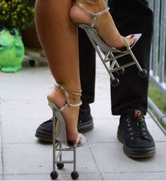 Do you see what the man is wearing on his feet?  He can probably pick up the woman when she falls off of these heels and breaks something...