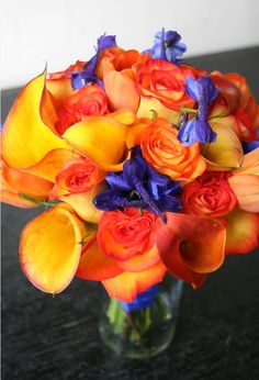 Flame mini Calla Lily, circus Rose, and blue delphinium, and orange tulip bridal bouquet