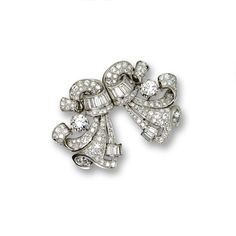 DIAMOND DOUBLE-CLIP/BROOCH, CIRCA 1950 Designed as a pair of scrolling drapery motifs, set with 2 round diamonds together weighing approximately 2.60 carats, further decorated with 139 round and single-cut diamonds and 16 baguettes weighing approximately 8.75 carats, mounted in platinum, separates into a pair of clips