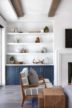White floating shelves over blue built-in cabinets display fine pottery and deco… White floating shelves over blue built-in cabinets display fine pottery and decor in a cottage living room beside a white beveled fireplace. Cottage Living Rooms, Coastal Living Rooms, Home Living Room, Living Room Decor, Coastal Cottage, Coastal Homes, Coastal Decor, Built In Shelves Living Room, Room Shelves