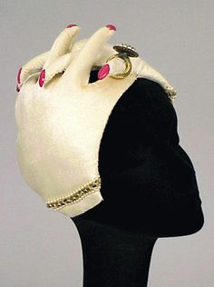 Bes-Ben clasping hands hat | Padded ivory velvet hands with applied red plastic fingernails, large pearl, and gilt-metal ring and pearl bracelets | Made in Chicago, United States.