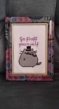 One fancy Pusheen cross stitch with the words Go Fluff Yourself on top. Comes with frame (frame may vary).