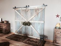 This double barn door is hanging in our family room. The door is made from reclaimed wood from an old homestead. Hung with hardware from RusticaHardware! It was hung on this wall because the wall is large and we wanted it to appear to go outdoors. But it is just an illusion.