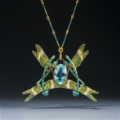 René Lalique. Dragonfly Pendant, circa 1903 depicting four dragonflies, with greenish-blue enamelled legs and wings set with diamonds and green and blue plaque-à-jour enamel, centering a large oval aquamarine.