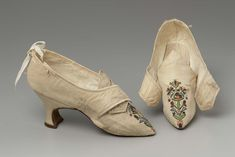 Pair of woman's shoes, Europe, late 18th century. White figured silk embroidered with polychrome silk and silver yarns and sequins in floral motif; latchets cross over pointed tongue; white silk binding along top and over side and back seams. Pointed toe. White figured silk covered Louis heel, top piece. Leather sole. Plain cotton insole and vamp lining, white leather quarter lining.