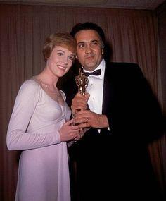 """Actress Julie Andrews poses with Italian film director Federico Fellini after presenting him with his Oscar at the 1963 Academy Awards at the Santa Monica Civic Auditorium in Los Angeles, Ca., April 13, 1964. Fellini won best foreign-language picture Oscar for his movie """"8 1/2."""" (AP Photo) / SF"""