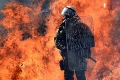 A fire bomb explodes behind a riot police squad in Athens. Officers clashed with hooded youths throwing firebombs on the sidelines of a large demonstration against a new round of austerity cuts