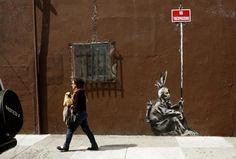 Una mujer pasa junto a un dibujo en la pared hecho por Banksy en San Francisco, California