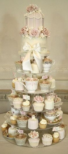 A tower of cupcakes in tea cups for easy serving, fans of cupcakes, and Alice In Wonderland themed weddings