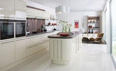 Cream gloss kitchen in a modern & uncluttered slab style.