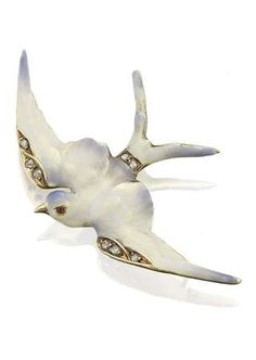 An Art Nouveau enamel and diamond swallow brooch, circa 1900. Modelled in flight, the outstretched wings in plique-à-jour enamel, the wings and tail with rose-cut diamond accents, wing span 42mm, stamped 15ct.