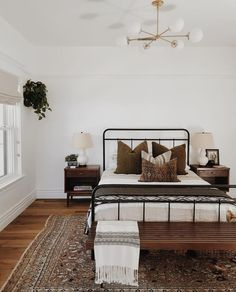 All neutral and brown bedroom with black iron bed, gold modern light,Moroccan rug, wood trunk