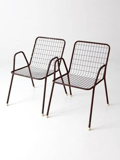 This is a set of two mid-century patio chairs. The brown metal frame chairs feature a wire metal seat and back. Sleek modern shape for your outdoor living. CONDITION In good, sturdy condition with wear consistent with age and use. Chairs show scuffs, scratches, and old welding repairs.