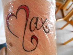 Tattoo of the name 'Max' with the 'M' shaped like a heart.