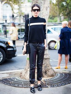 Leila Yavari wears a striped black sweater with baggy leather pants and patent leather loafers
