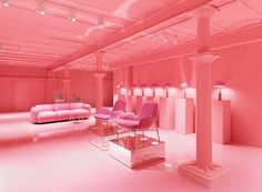 A metal shaft in the middle of a Normann Copenhagen homeware store reveals a gallery with an all-pink interior below it.