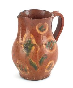 """Realized Price: $ 2133    Berks County, Pennsylvania redware pitcher, early 19th c., with yellow and green floral slip decoration, 7 1/2"""" h."""