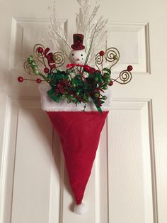 Santa hat door decor for under $10-Dollar store hat, brick of foam, 6 floral picks on sale 50% off-fill the front only! The way it hangs you cannot tell it's not full up! Clip a binder clip on the back  and hang it over the wreath hanger or a nail!!!