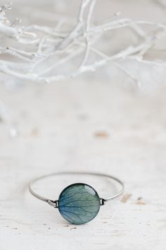 Gorgeous sky blue bracelet with a round cabochon with a print of fragment of hydrangea petal