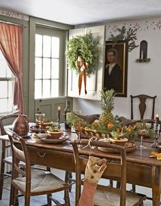 The centerpiece — fresh fruit tucked into a basket of pine boughs — is historically appropriate as pineapples were a Colonial American symbol of hospitality and citrus fruit was a holiday delicacy often tucked into children's stockings.