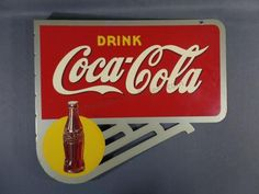 "1940's Coca Cola double sided wall mount flange sign with caption ""Drink Coca Cola"" and a upright coke bottle over yellow. The sign is marked on both sides American Art Works initials ""A.A.W - 6 - 2"" - ""Made in U.S.A."" and Trade Mark Reg. U.S. Pat.Off."". The sign has nearly no age and use marks present. Measures 20 1/2"" tall x 24"" long. From the collection of an avid Coca Cola collector and Coca Cola Club Member. The sign can be found in..."