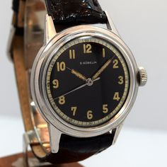 A 1940's era stainless steel Gueblin military timepiece with a patinated black dial and luminous Arabic numerals. Gueblin was a renown Swiss jeweler who dealt in Patek and LeCoultre mostly, but also manufactured watches for the Royal Air Force and other military personnel. (Store Inventory # 9956, listed at $1250).  #egubelin #gubelin #military #black #dial #vintage #wristwatches #watch #watches #stawc