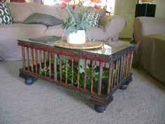 This is an old chicken crate that I found at an antique store.  I cleaned it and stained it.  Then put legs and glass on it to make a cute coffee table.  I put a few fake moss and succulents in for a warm look.