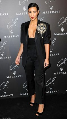 Sleek and chic: Kim opted foran androgynous black trouser suit and wore a giant embellish...