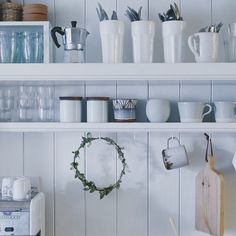 open white kitchen shelves with white and glass kitchenwares and wreath