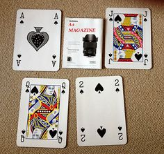 Large playing cards beside A4 magazine for scale